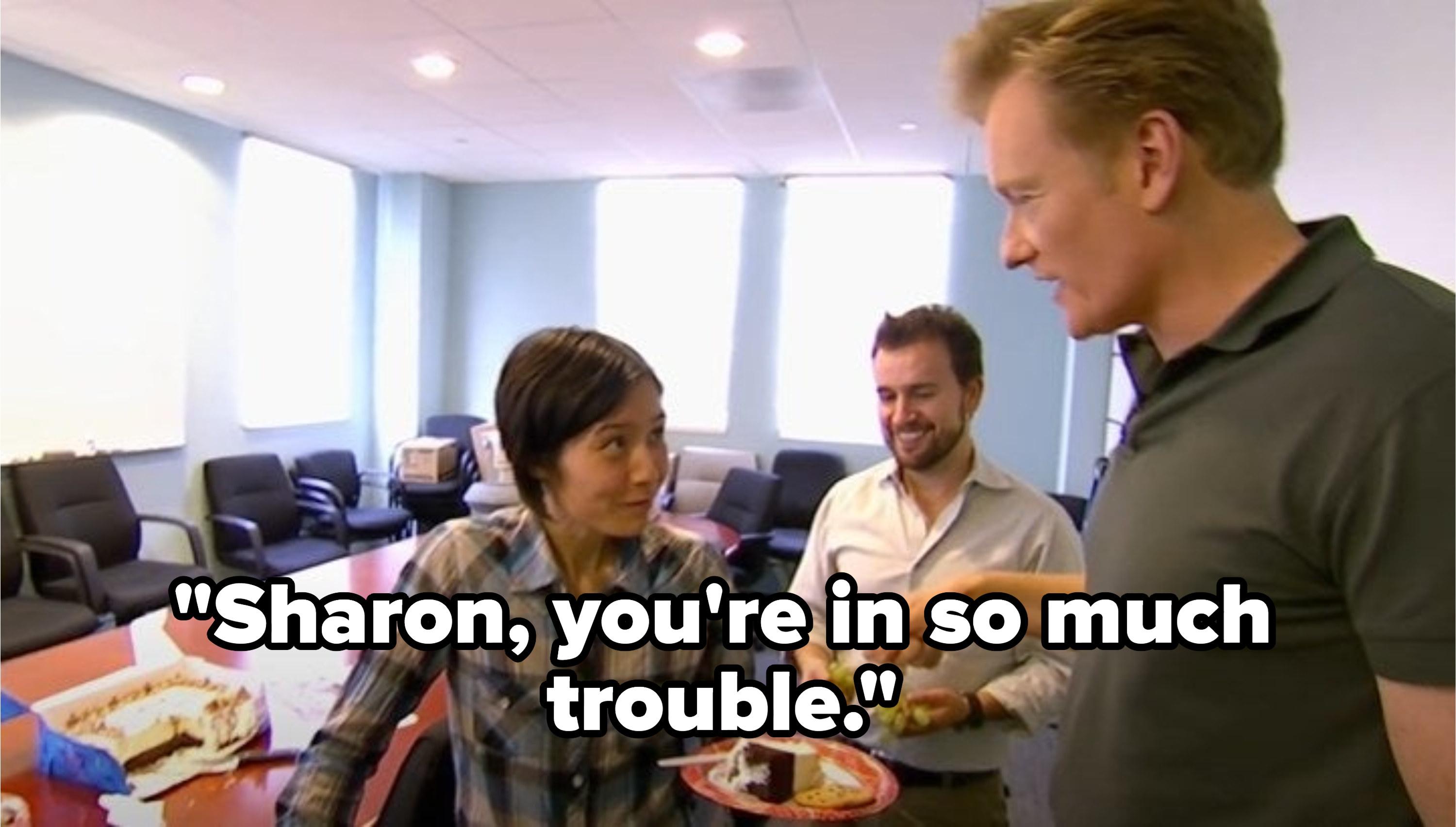 Conan talking to a staff member that's eating cake