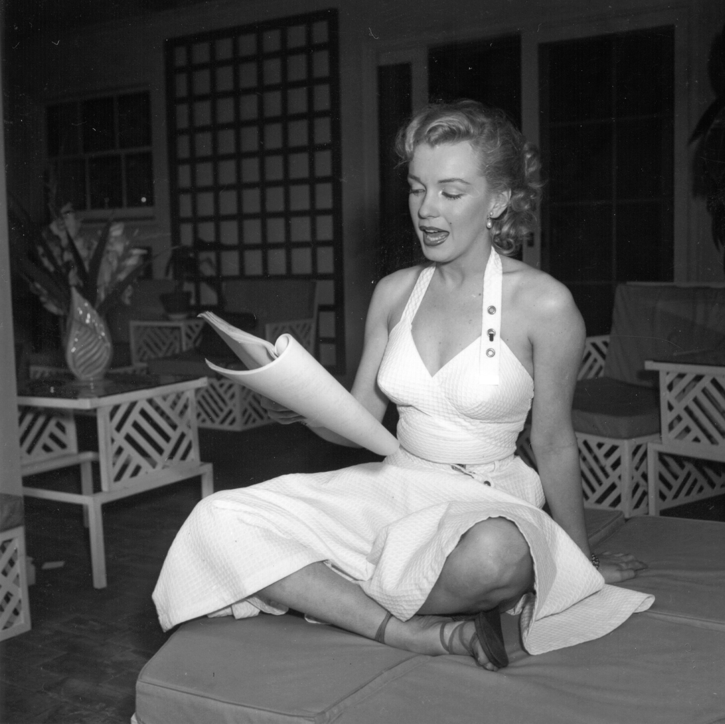 Marilyn Monroe sits with her legs crossed and reads a book