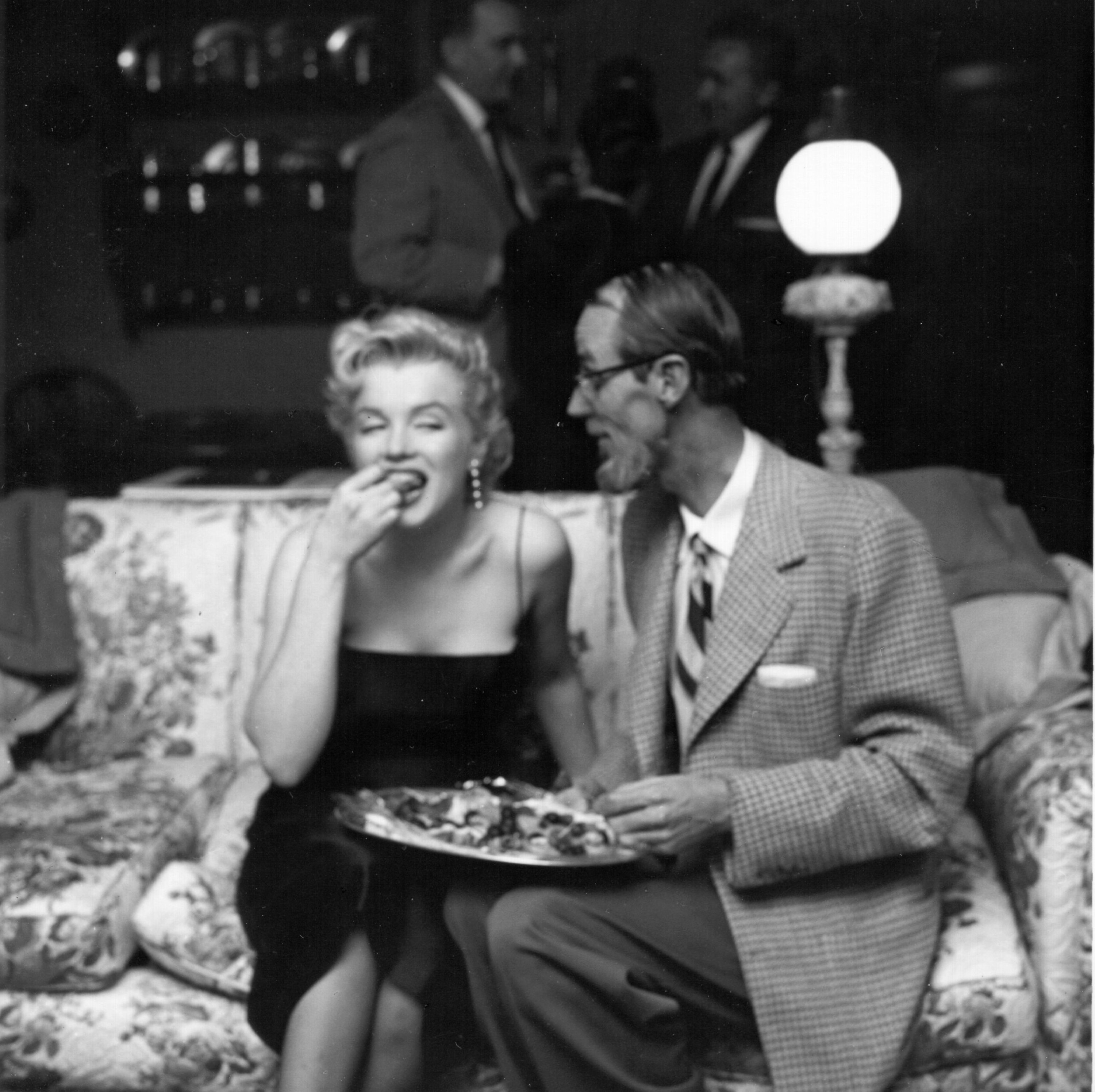 Marilyn Monroe eats and sits on a couch next to a man