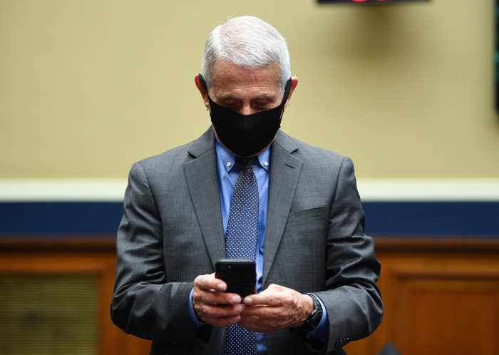 Anthony Fauci, wearing a face mask, looks down at his cellphone in his hands