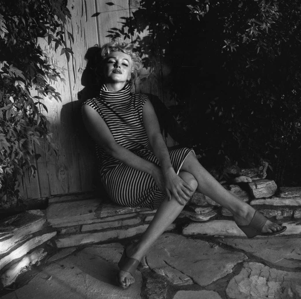 Marilyn Monroe sits outside in a striped dress