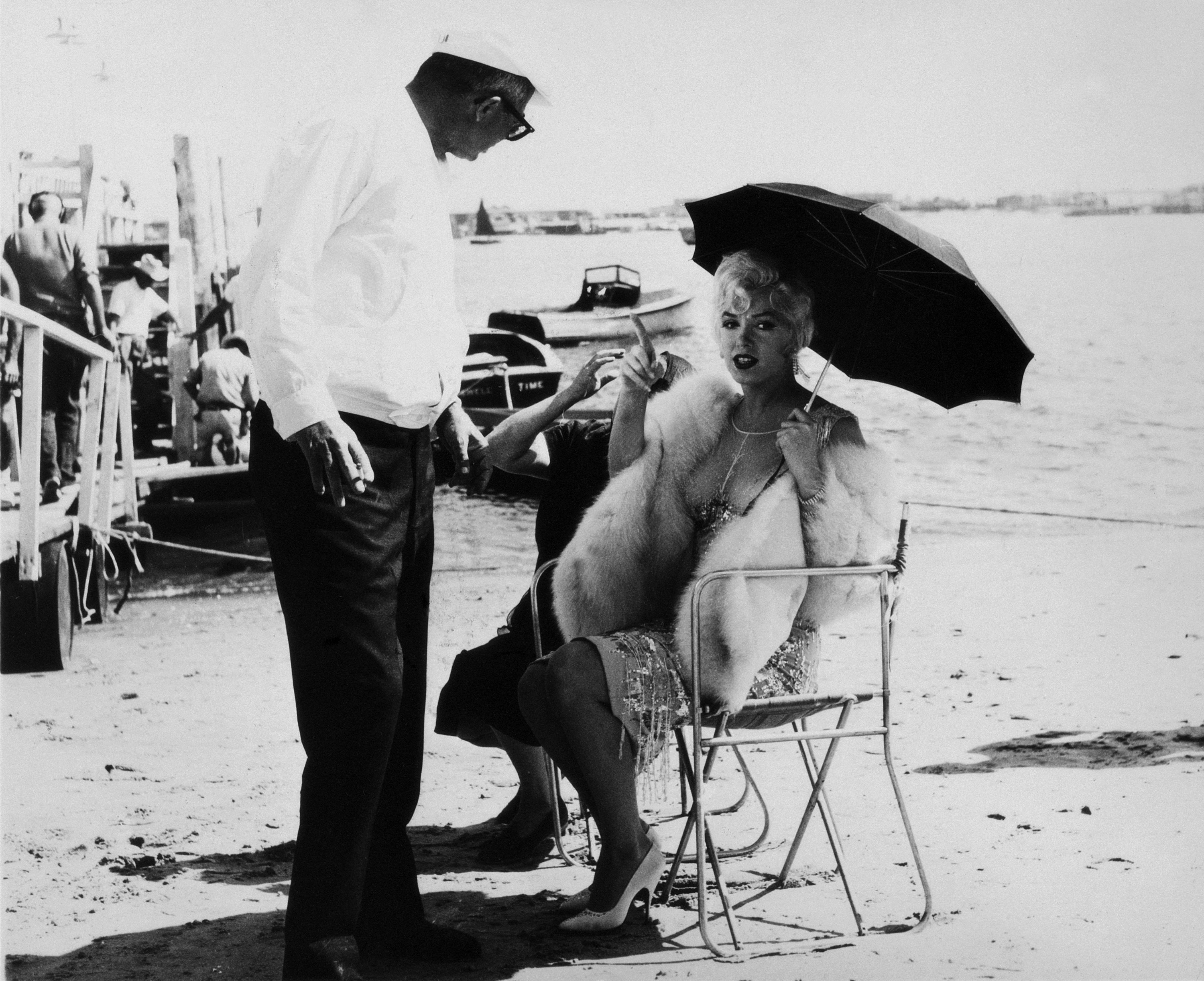 Marilyn Monroe on a movie set under a parasol talking to the director