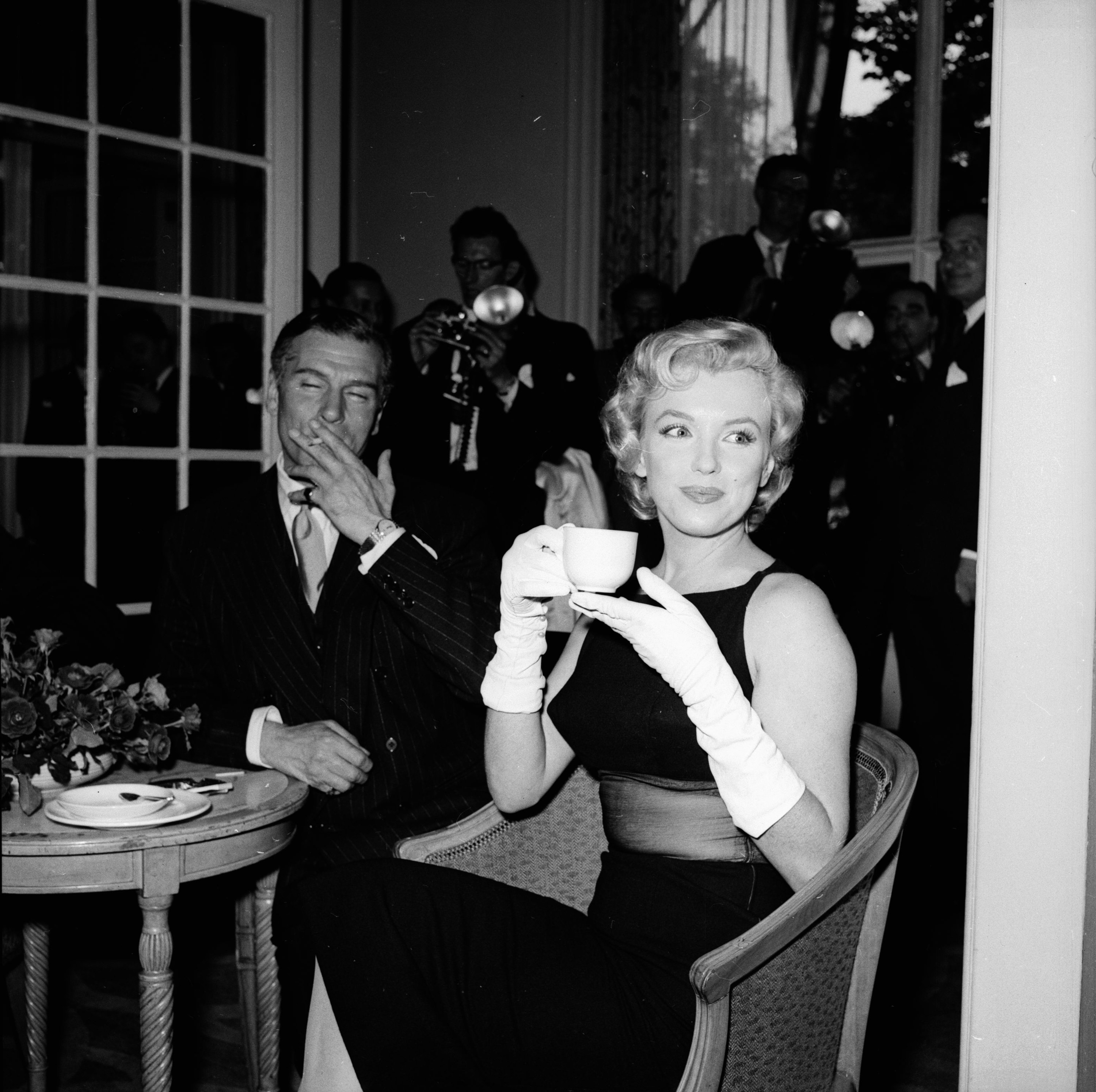 Marilyn Monroe sipping tea and wearing long gloves at a party