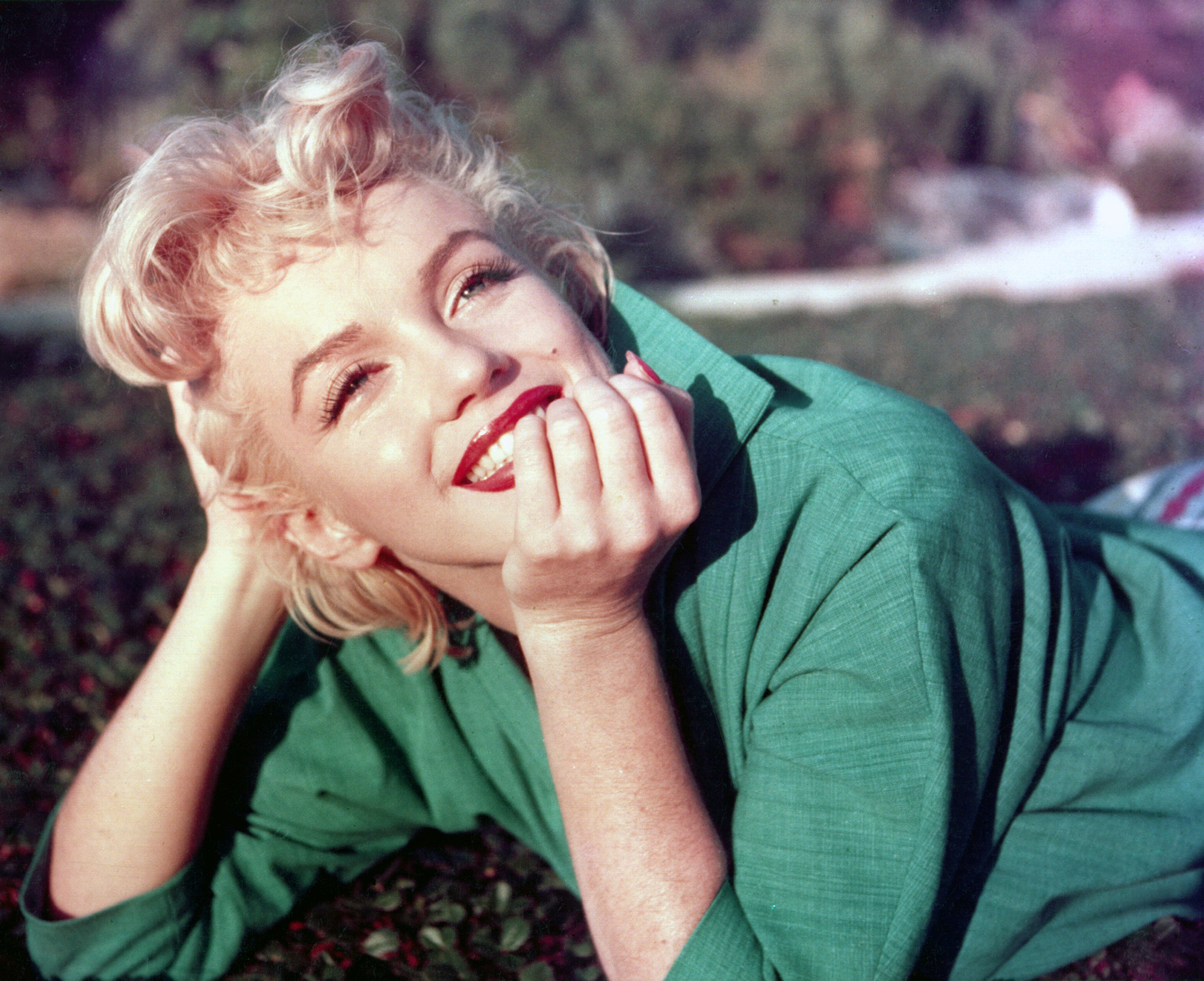 Marilyn Monroe lying on the grass in a suit