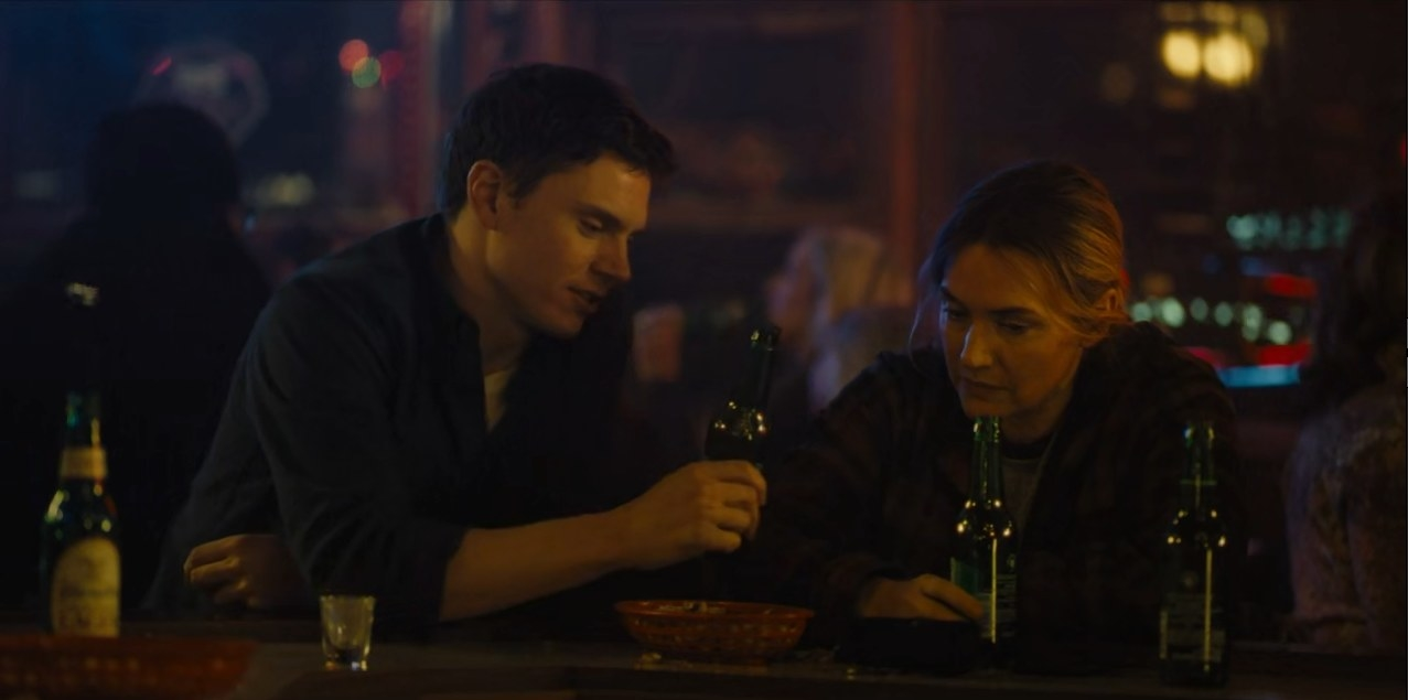 Colin Zabel (Evan Peters) clinking Rolling Rock beer with Mare (Kate Winslet)