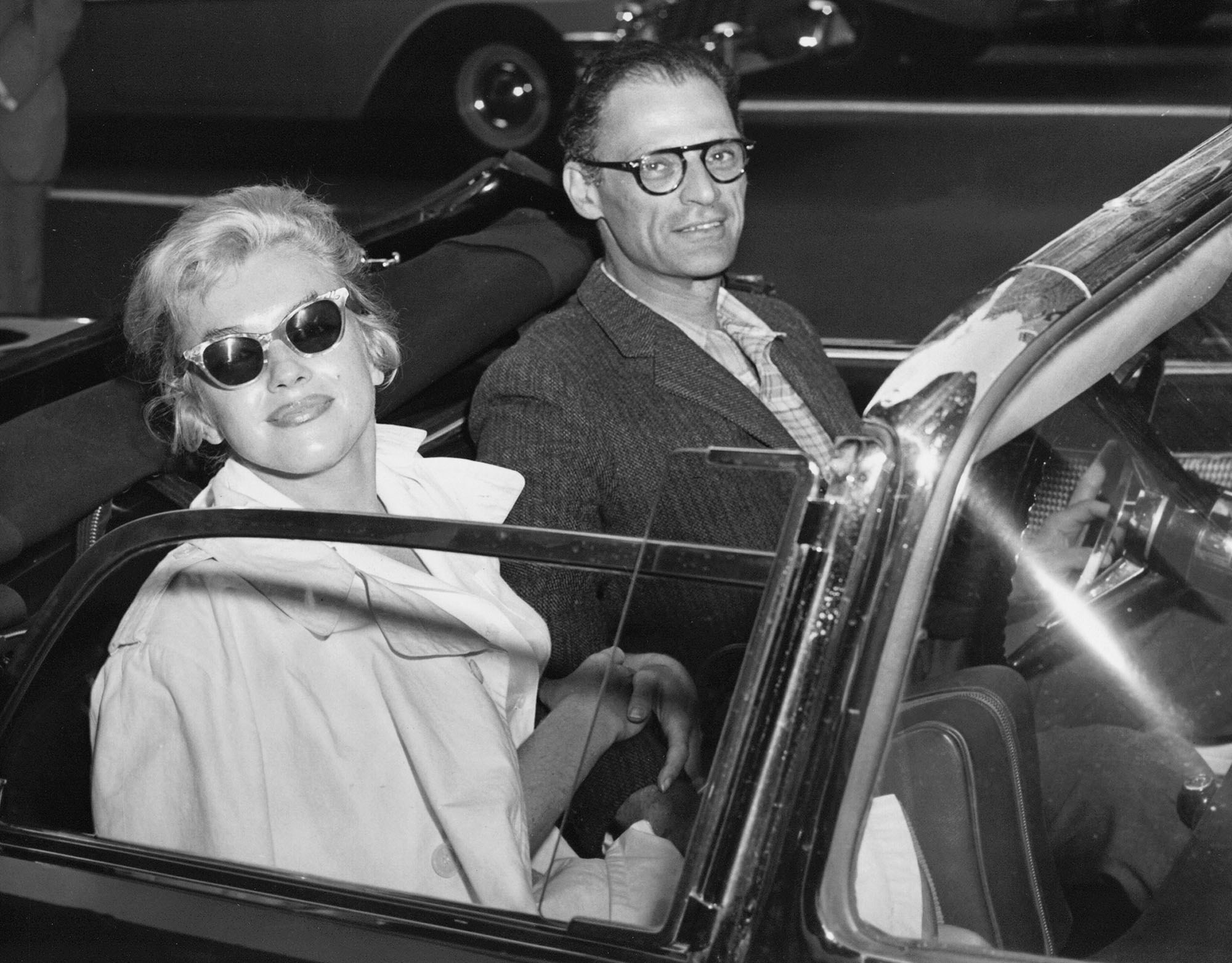 Marilyn Monroe, wearing sunglasses, smiles at the camera from the passenger seat of a convertible