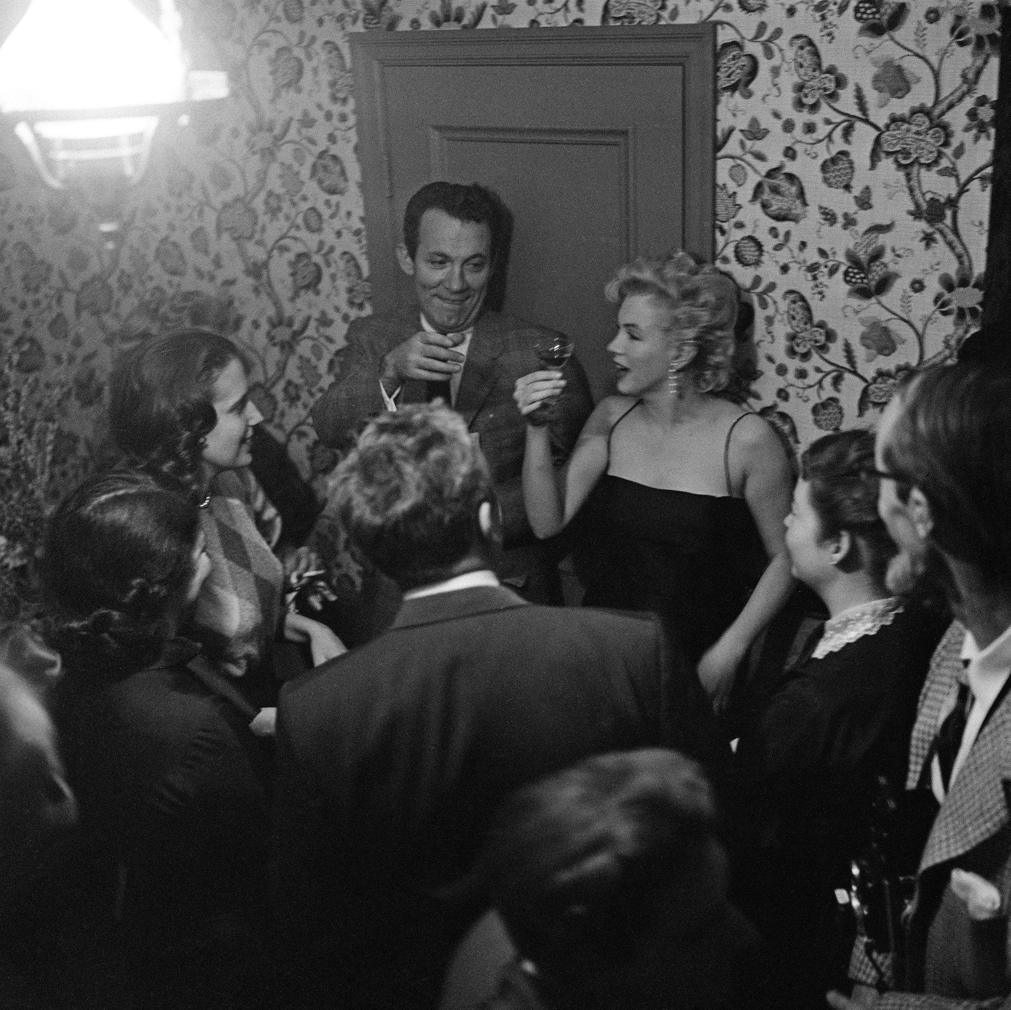 Marilyn Monroe holds up a small glass of alcohol, surrounded by people at a party