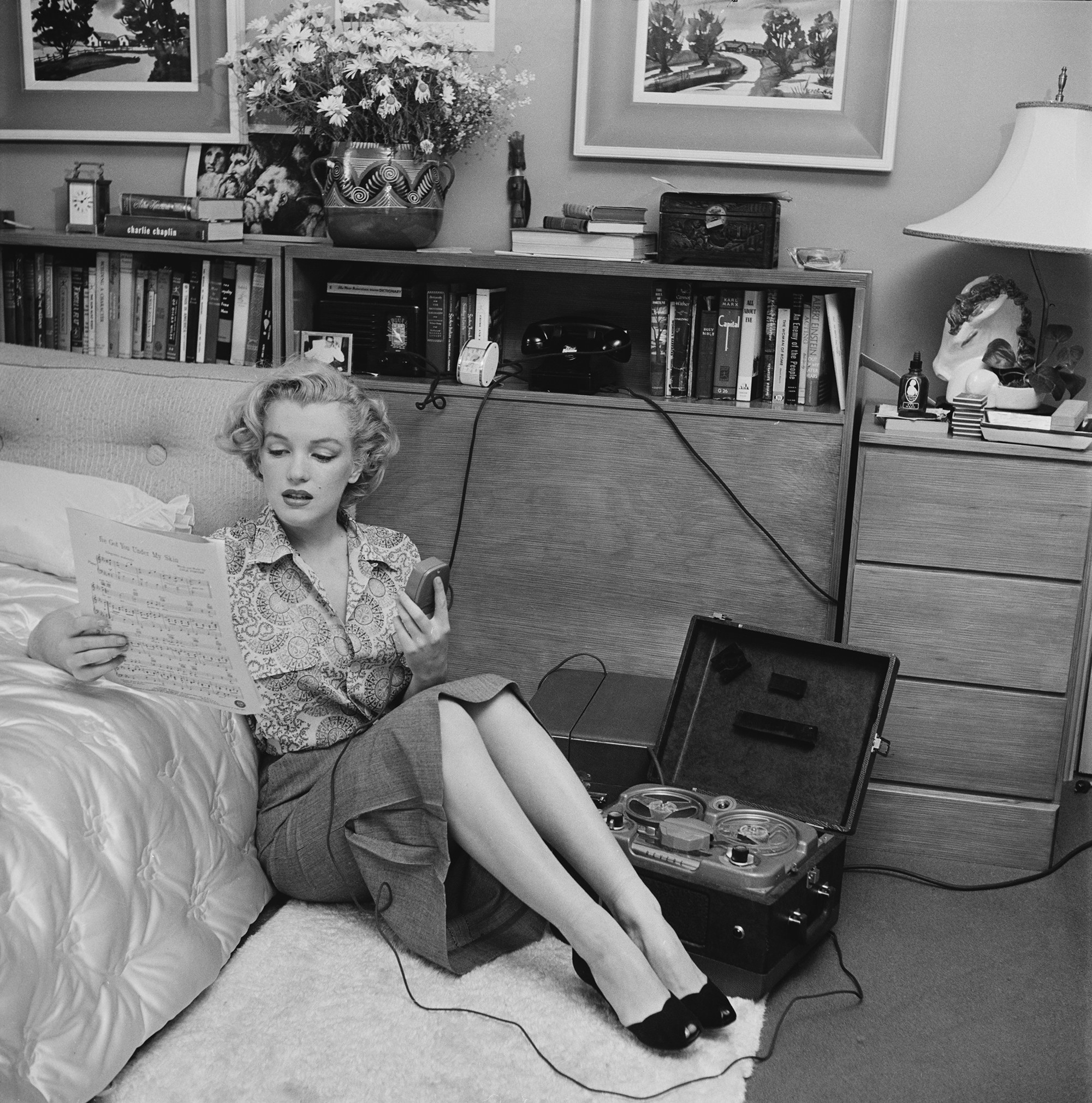 Marilyn Monroe holds a microphone and sits on the floor next to a recording device