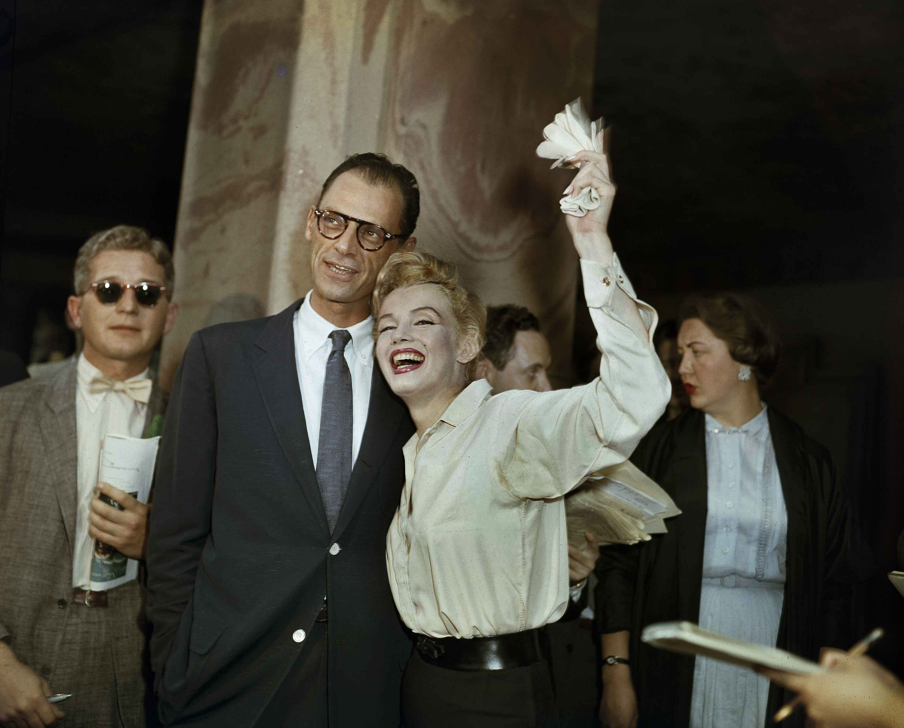 Marilyn Monroe smiles widely and waves her gloves in one hand as she stands next to her husband Arthur Miller