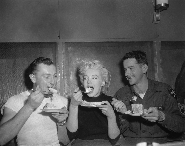 Marilyn Monroe eating between two soldiers