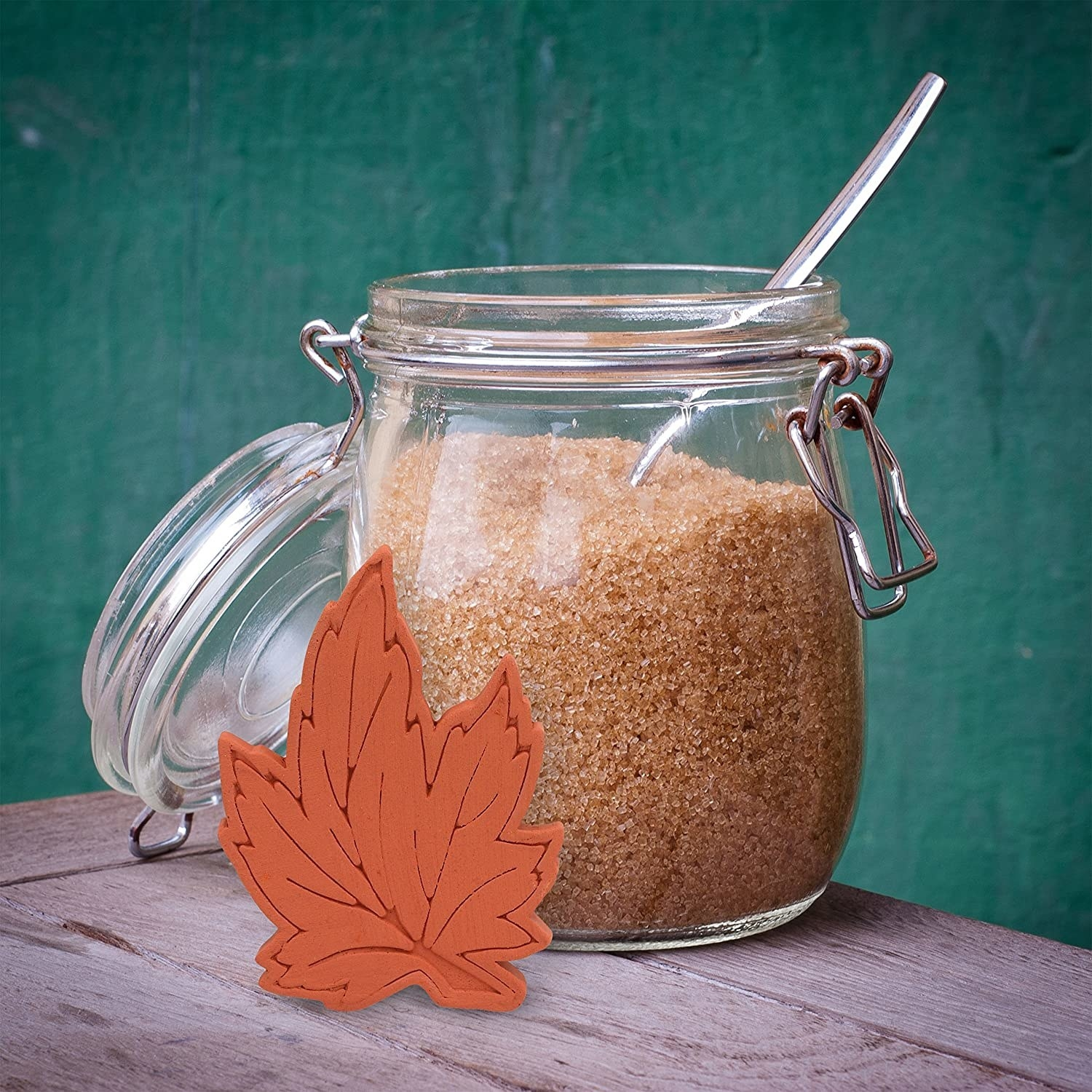 glass jar of brown sugar with a leaf shaped terra cotta piece beside of it