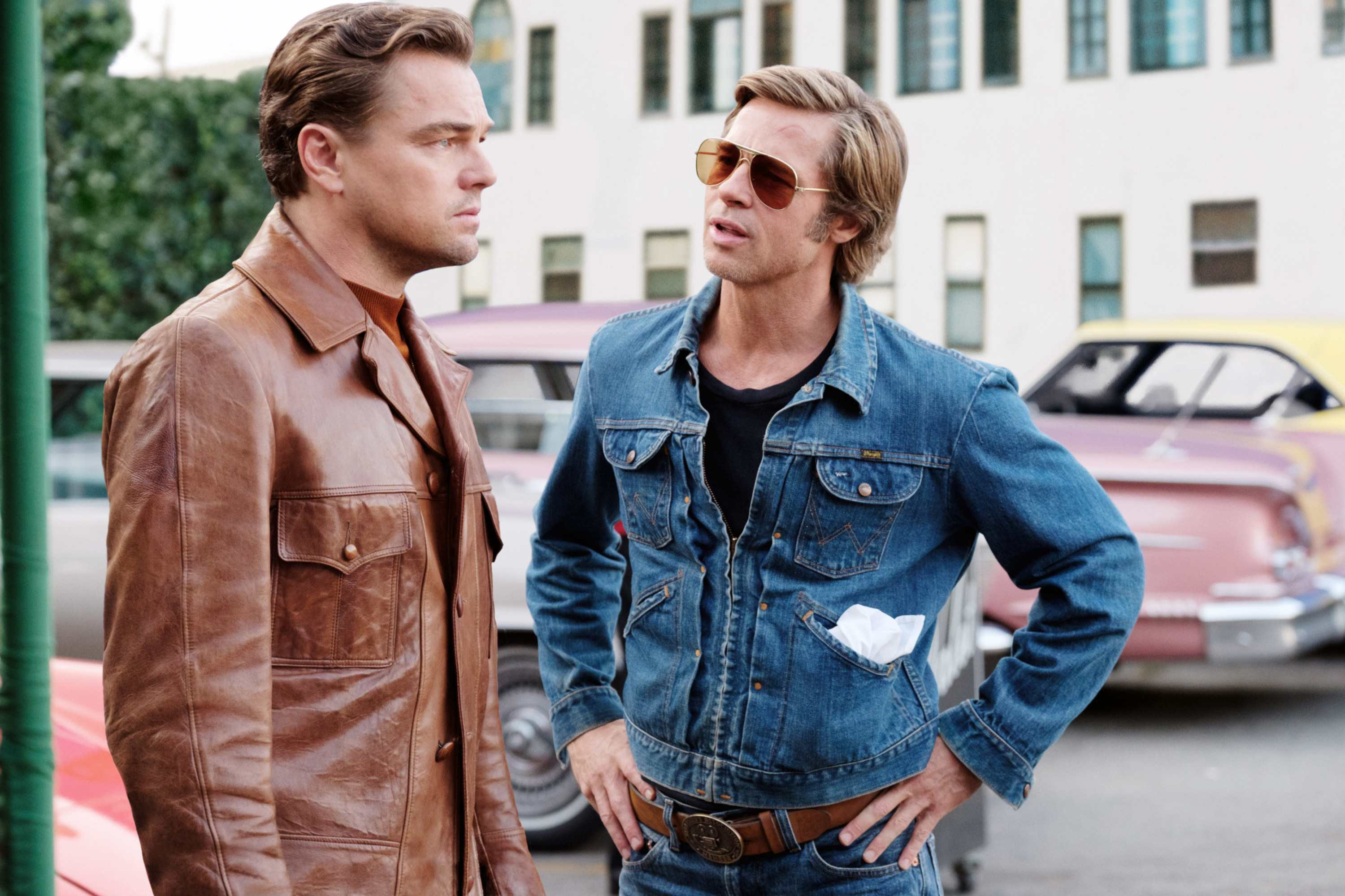 """Bradd Pitt and Leonardo DiCaprio standing in a parking lot in """"Once Upon a Time in Hollywood"""""""
