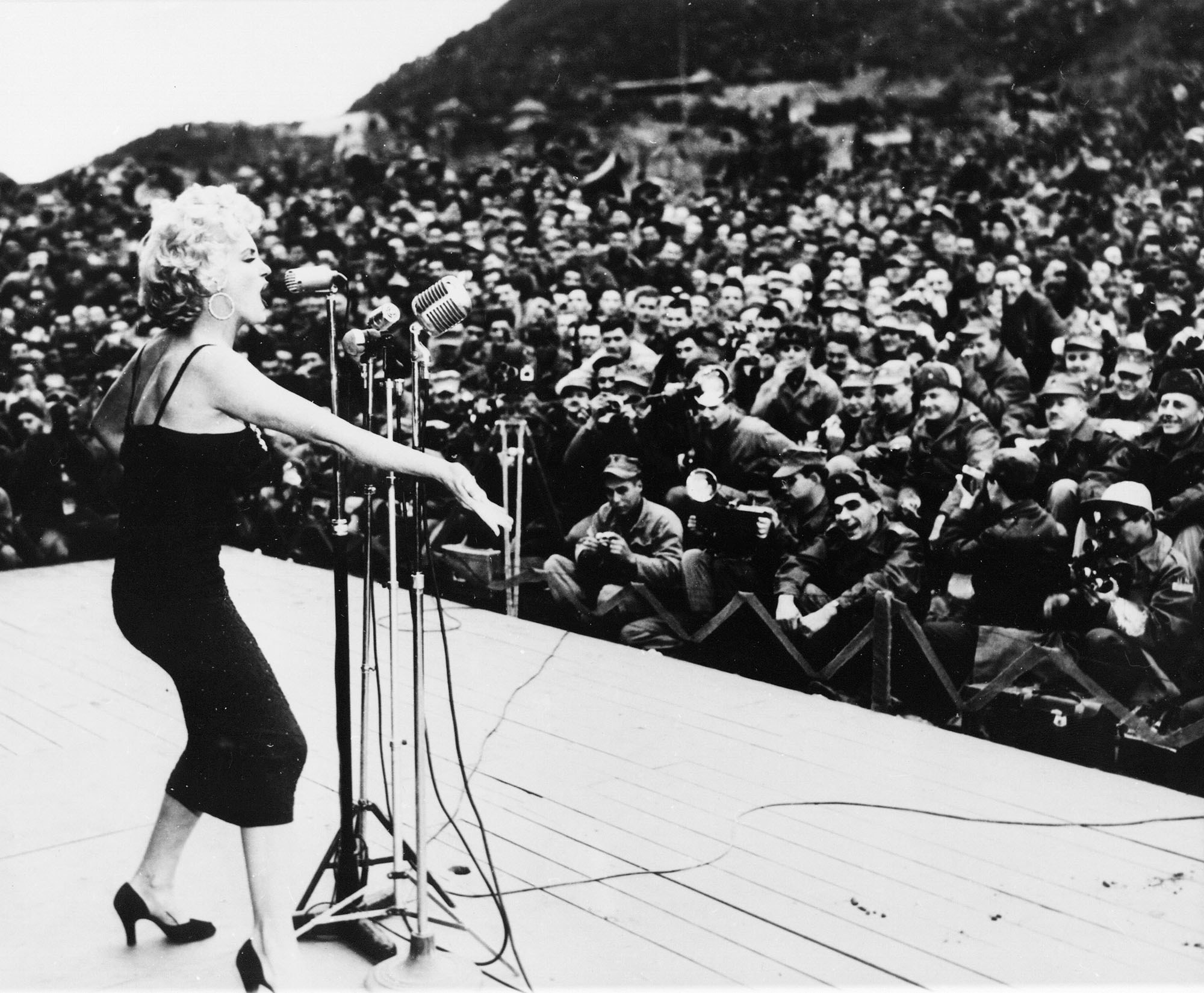 Marilyn Monroe, wearing a dress and heels, stands behind a microphone and faces hundreds of service members
