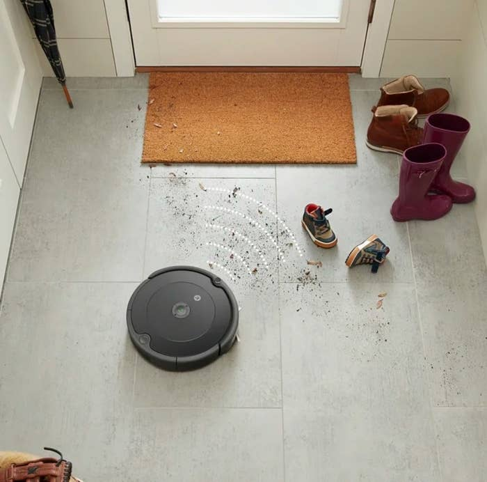 An iRobot Roomba cleaning dirt off the floors in a foyer