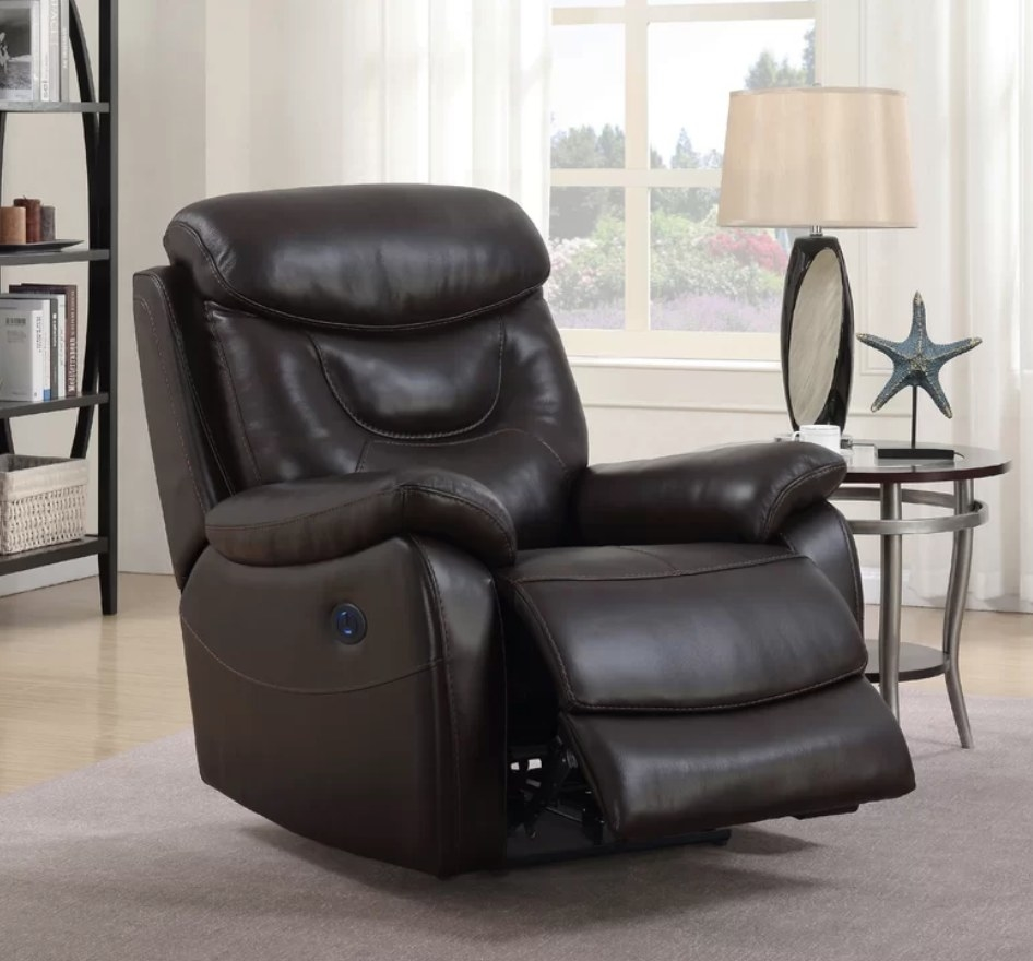A dark brown, leather recliner with the foot rest slightly elevated in a living room