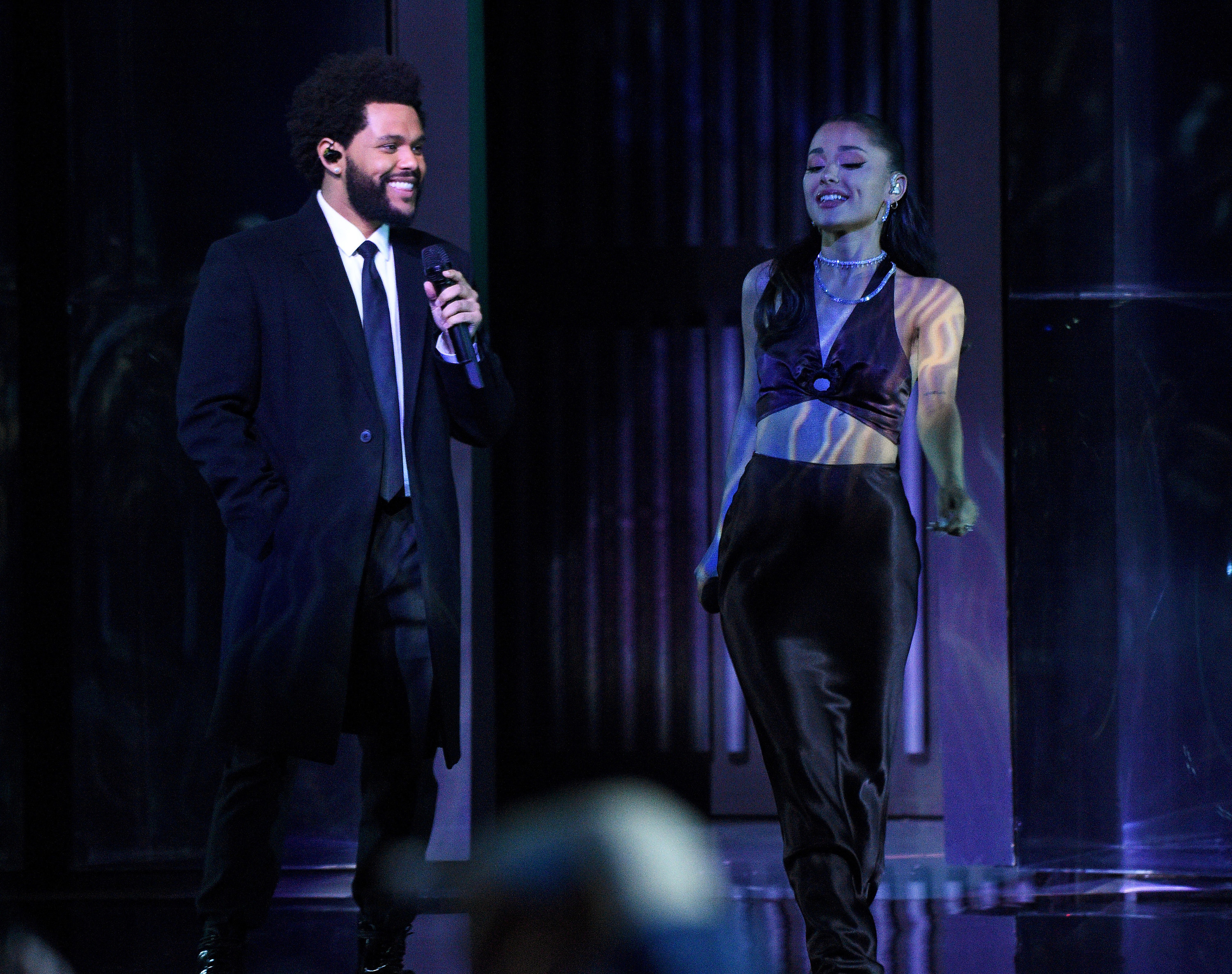 Ariana stands next to The Weeknd while performing