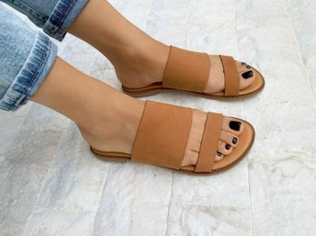a model wearing the sandals in brown