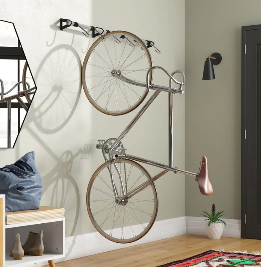 A black and silver, 6-hook, wall-mounted bike rack with one bike hanging from it
