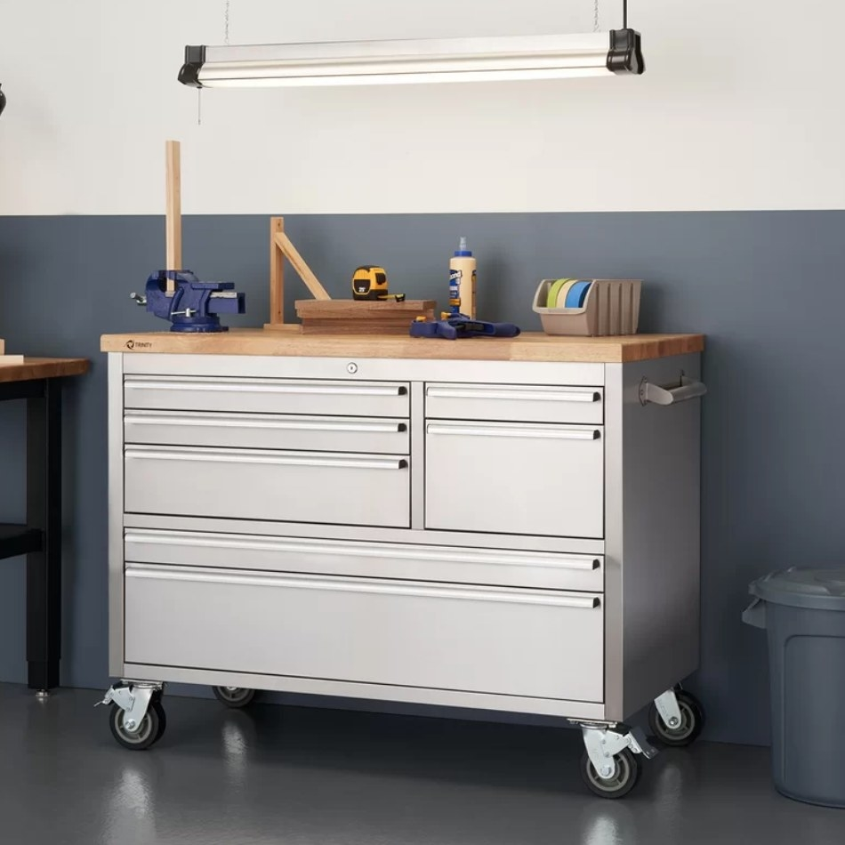 A white, stainless steel workbench with four wheels and tools on top inside a garage