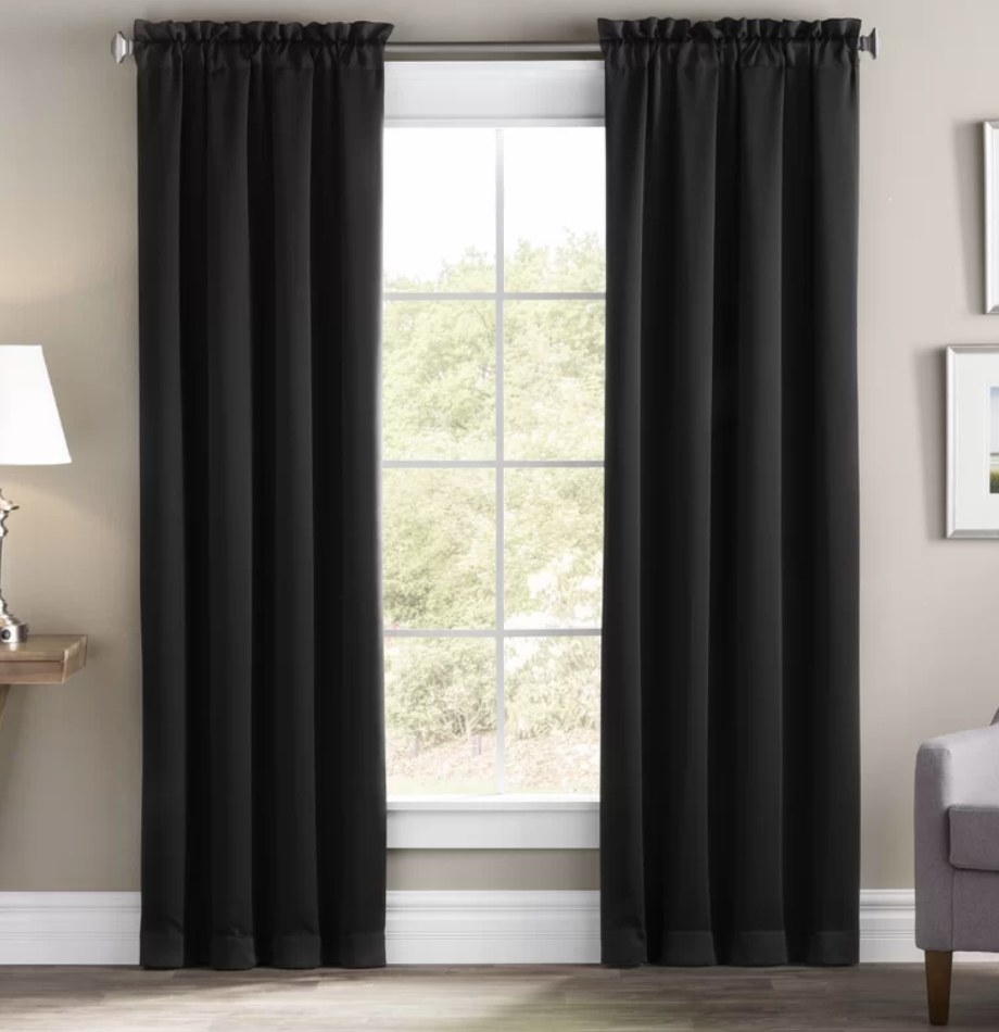 A set black, blackout curtains hanging from a rod over a window in a living room