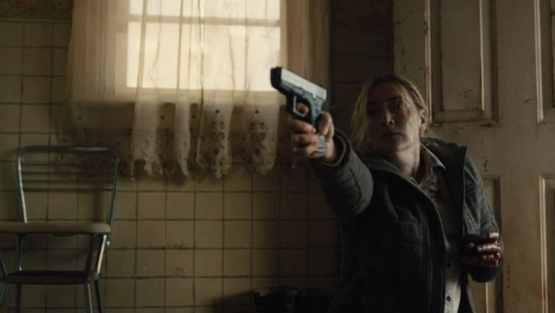 Mare (Kate Winslet) holding a gun in the miniseries