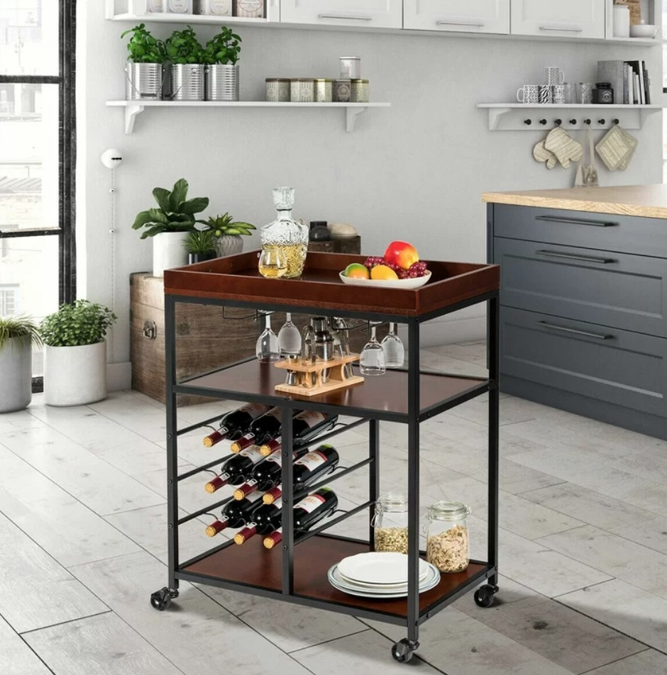 A brown and black bar cart on four wheels with 3 shelves and a rack that fits 9 bottles of wine inside of a kitchen