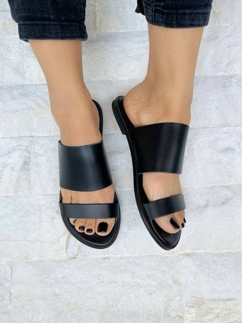 a model wearing the sandals in black