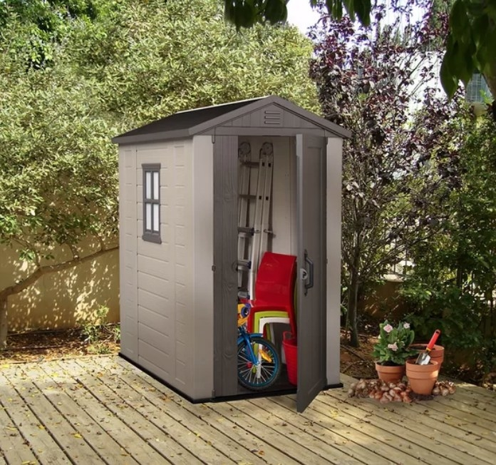 A brown/taupe, plastic tool shed outside and filled with a ladder, bike, chairs, and other items