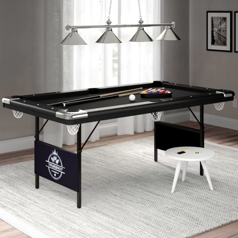 A black, folding pool table with two cues, a ball rack, and a complete set of pool balls
