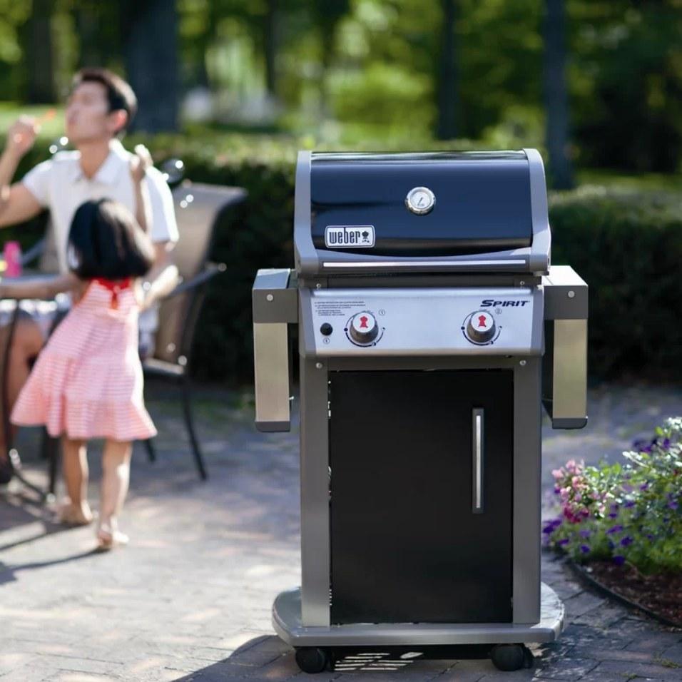 A liquid propane, gas grill outside in a family's backyard