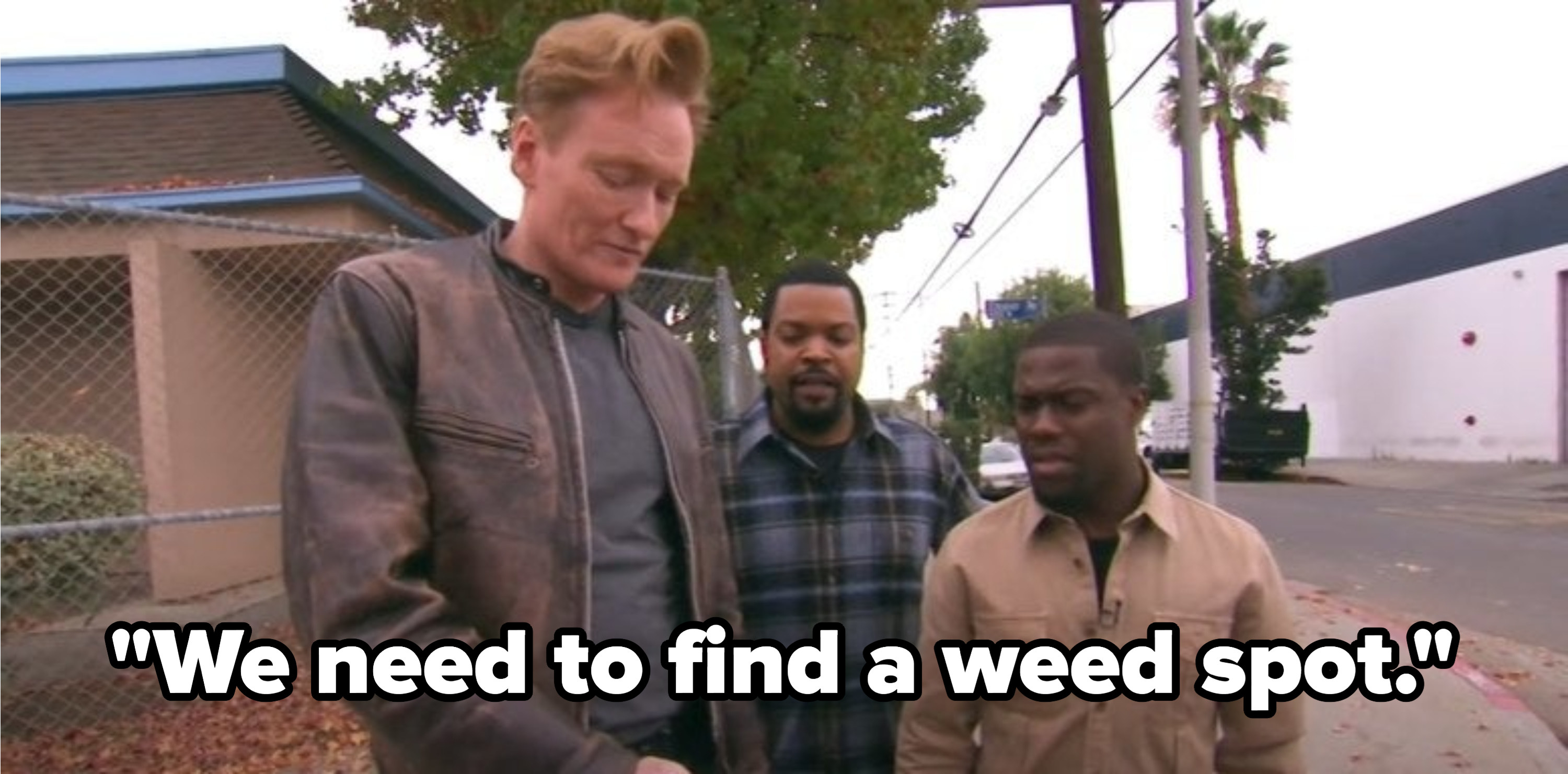 Conan, Ice Cube, and Kevin Hart looking at a phone on a street corner