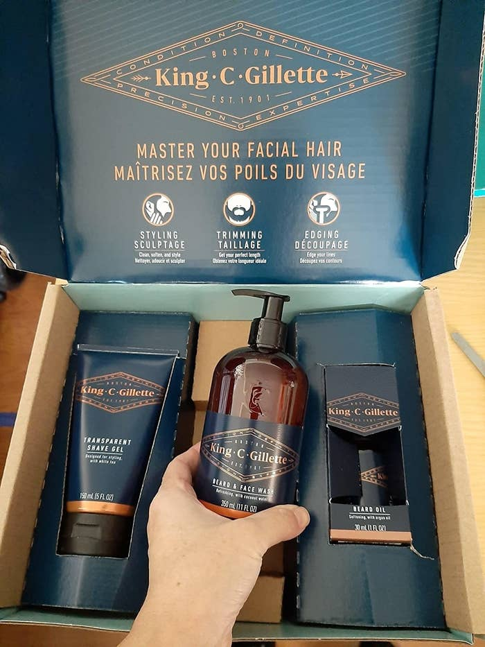 a reviewer holding the beard wash in front of the kit