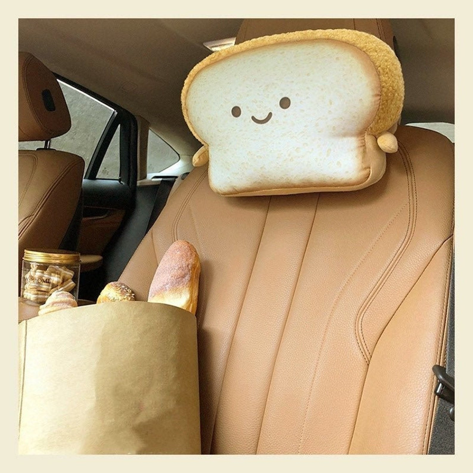 cartoon toast looking neck pillow attached to a car seat headrest