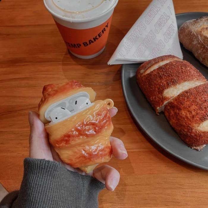 person holding an airpods case with a croissant-shaped cover