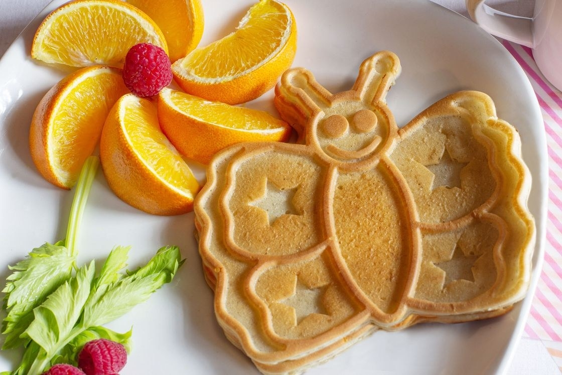 a butterfly-shaped pancake on a plate with orange slices arranged like a flower