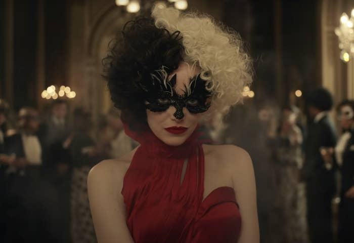 A screenshot from the movie of Cruella wearing a red gown