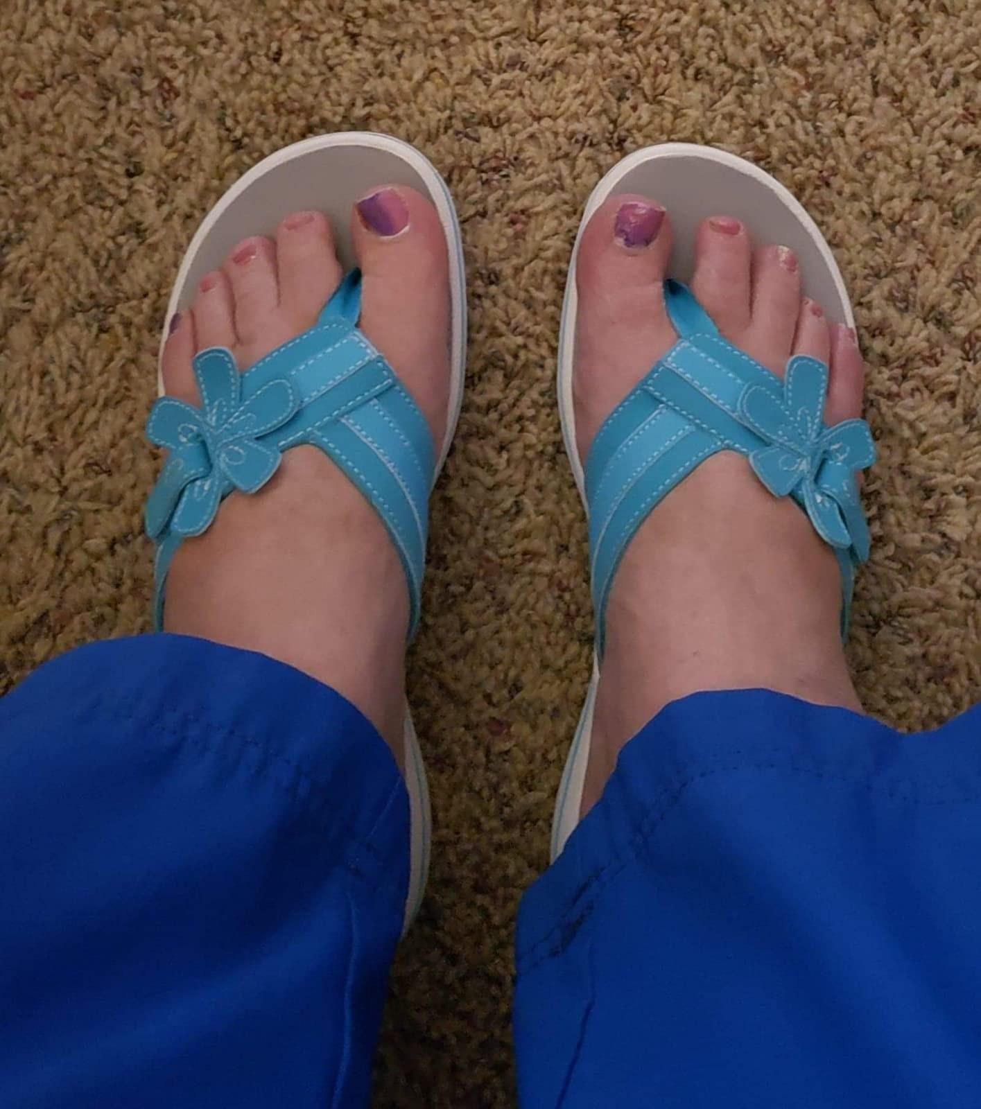 Reviewer wearing blue Clarks flip-flops with flower detail