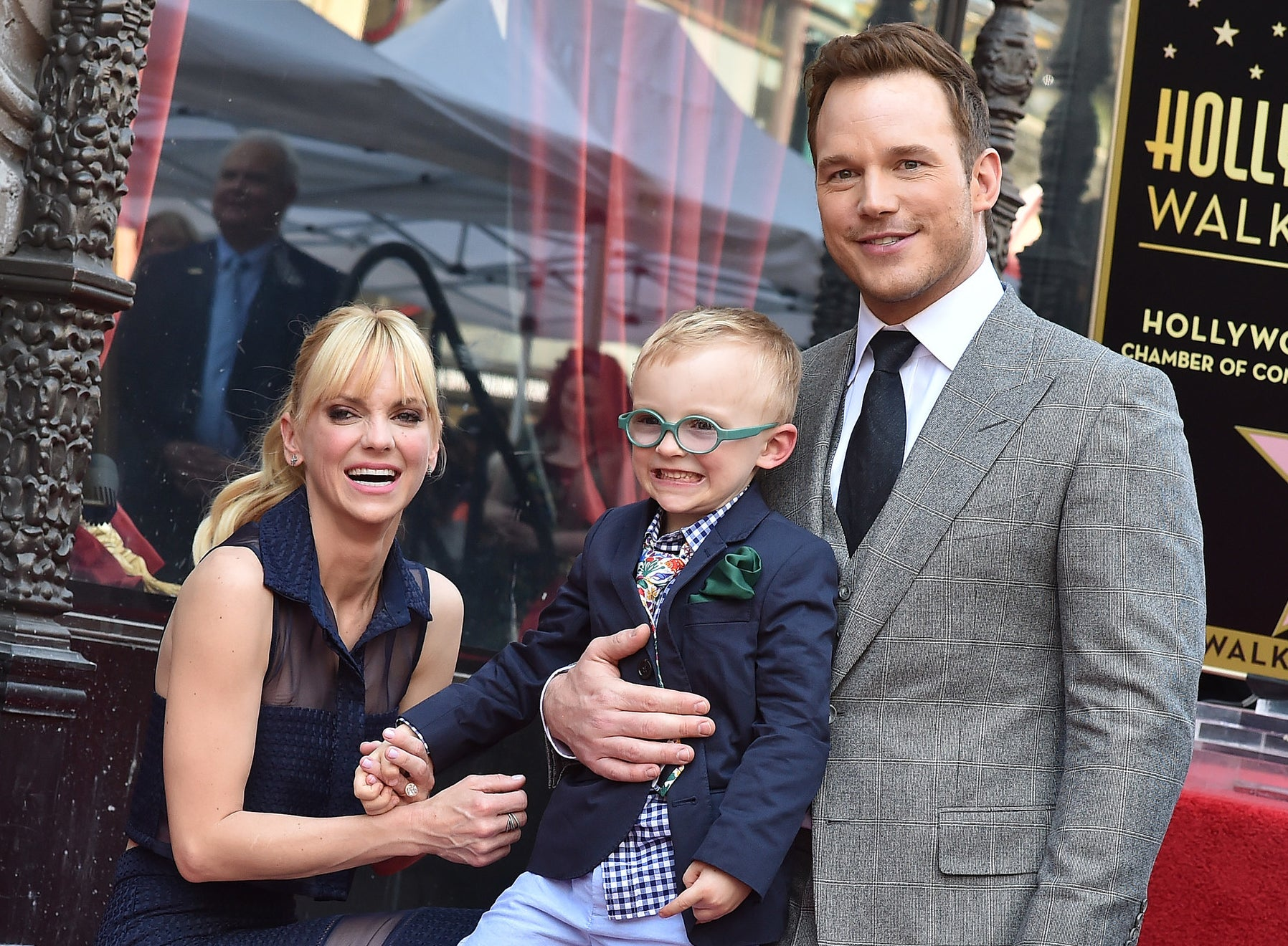 Chris and Anna hold hands with Jack at an event