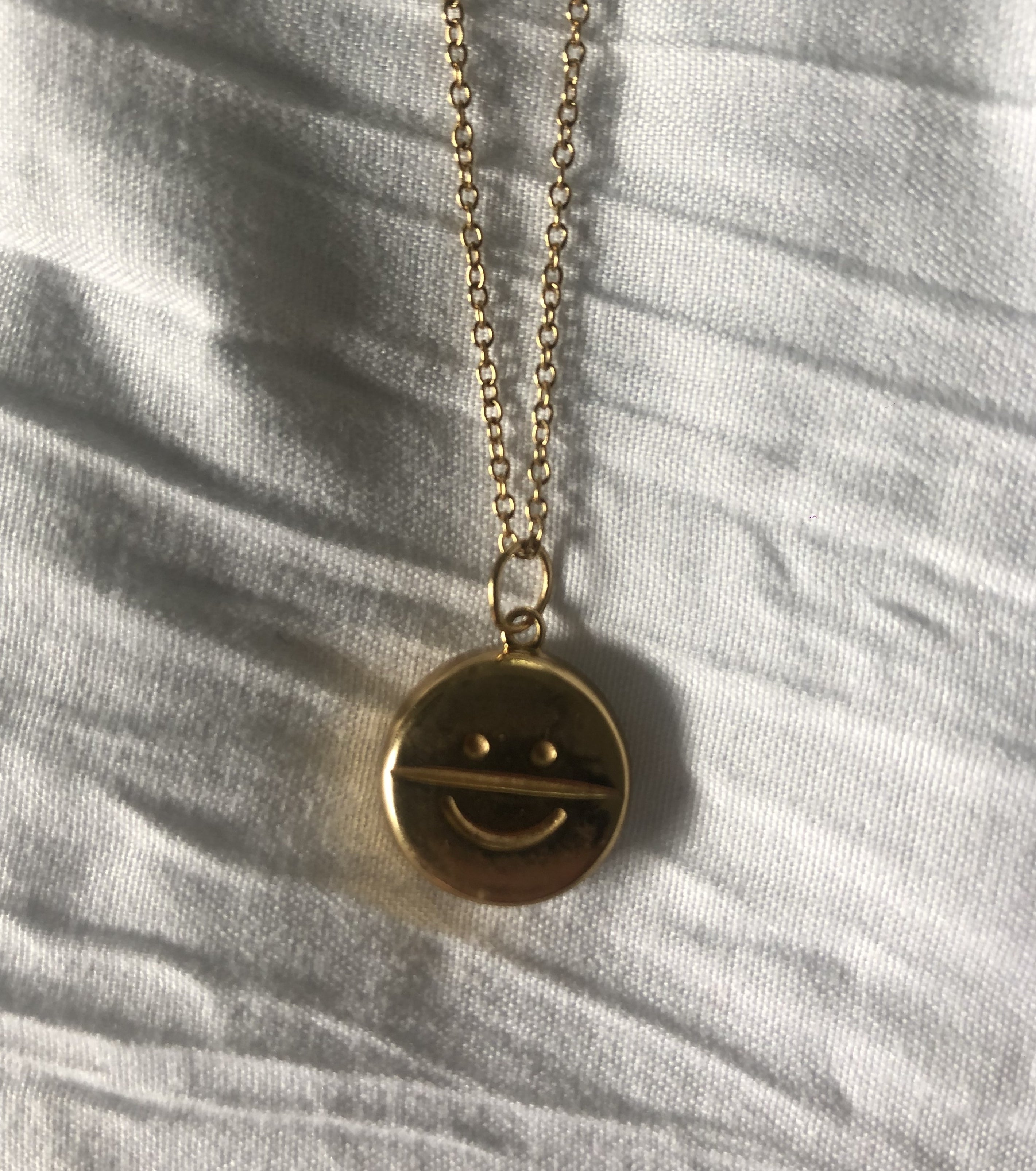 gold necklace with a gold charm of a smiley face on an antidepressant pill