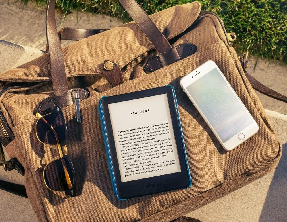 kindle styled on top of a beach bag with sunglasses and cell phone