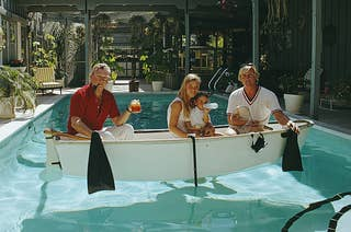 Four people in a rowboat in a pool
