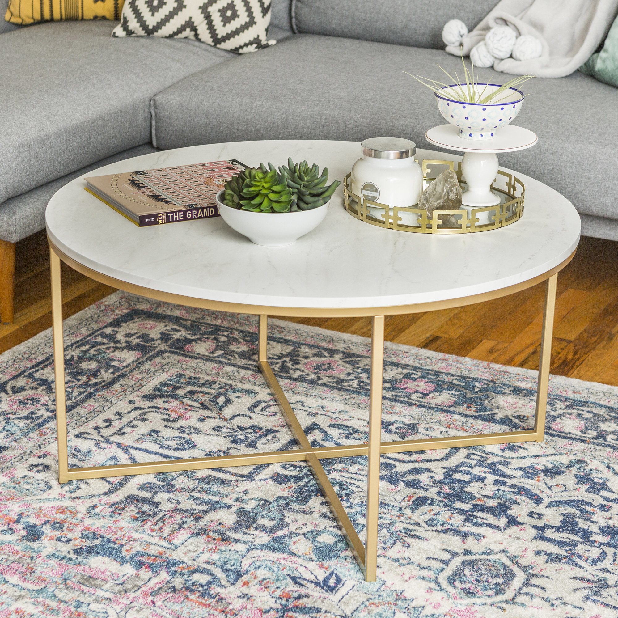round coffee table with white marble top and gold legs