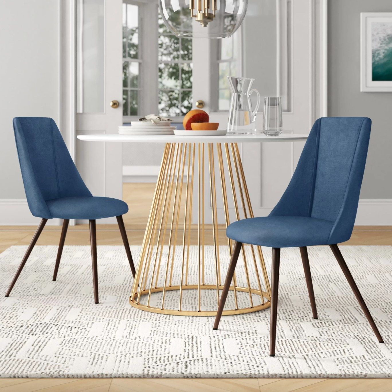 the set of two velvet upholstered chairs in blue with brown wood legs