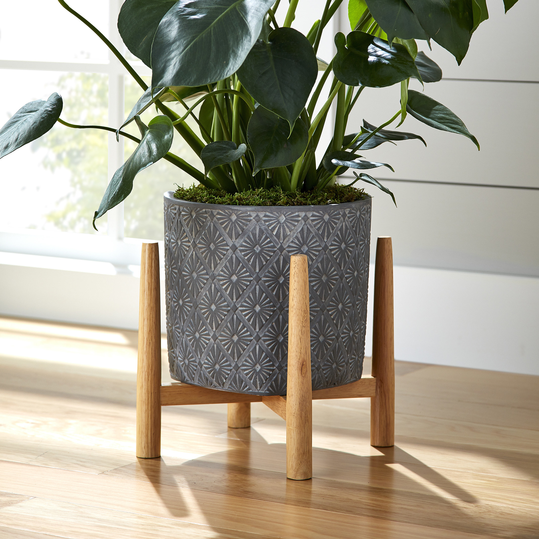 gray pot with geometric design and wooden stand