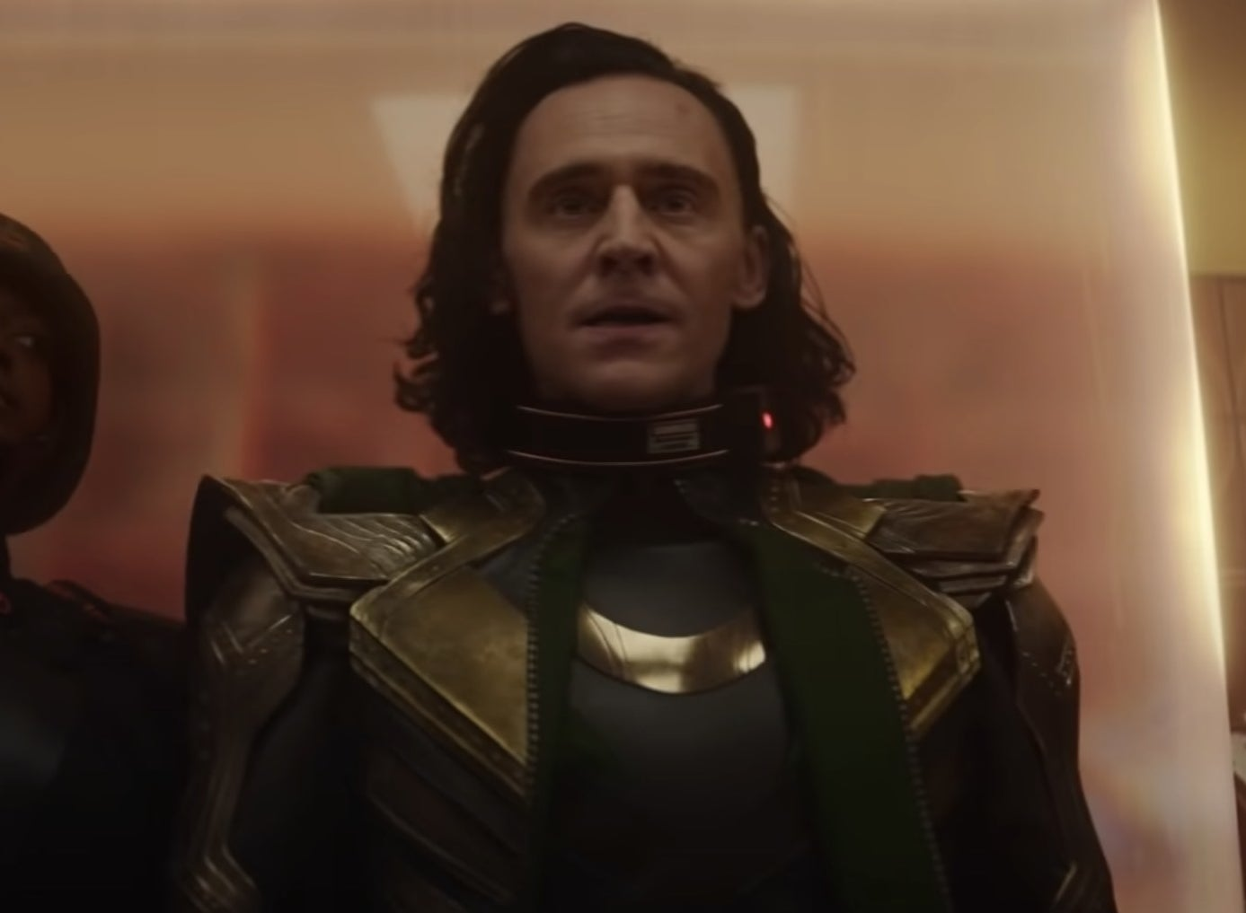 A screenshot of Loki being escorted into a building by a guard