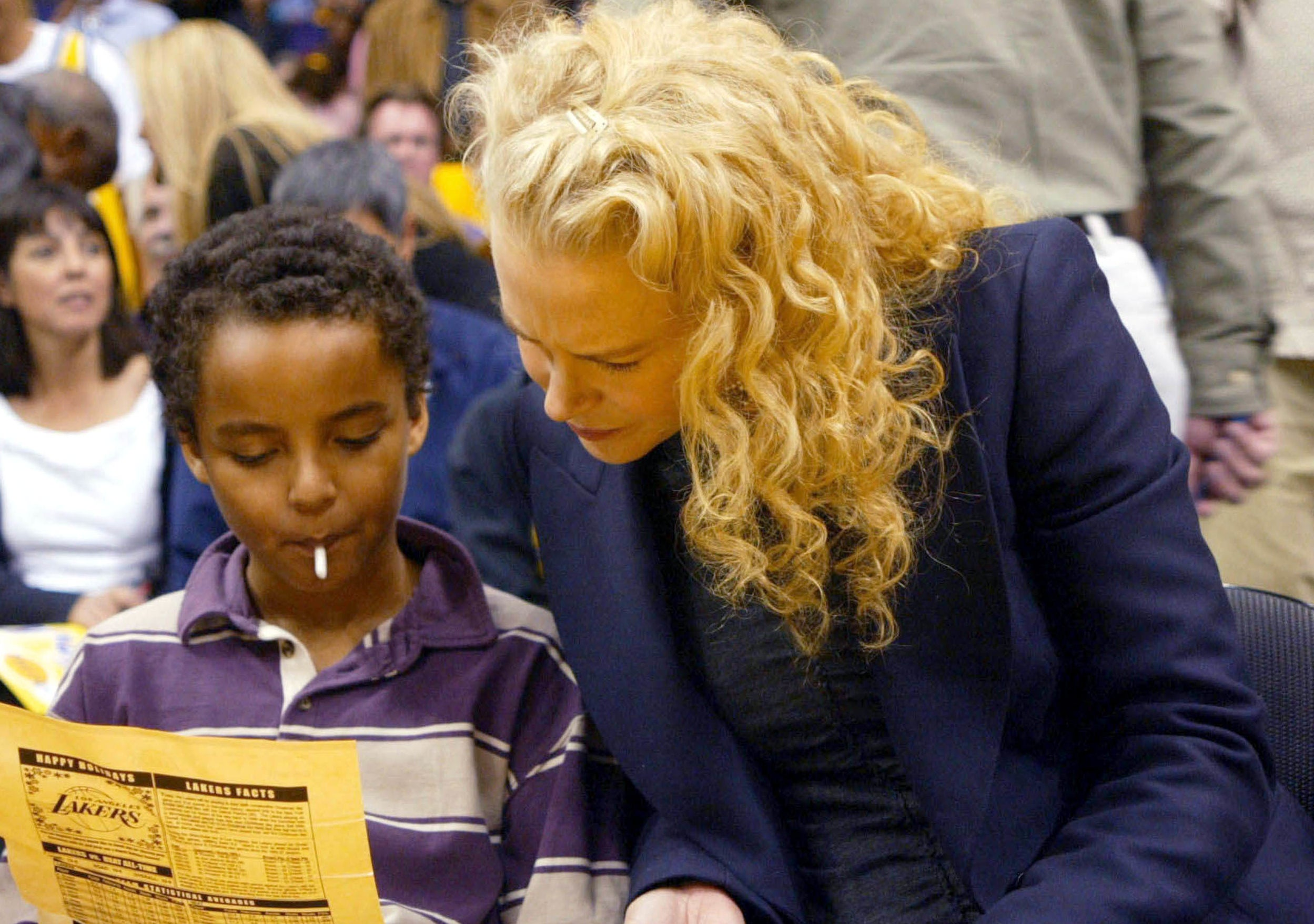 Nicole reads a piece of paper with a young Connor at a basketball game