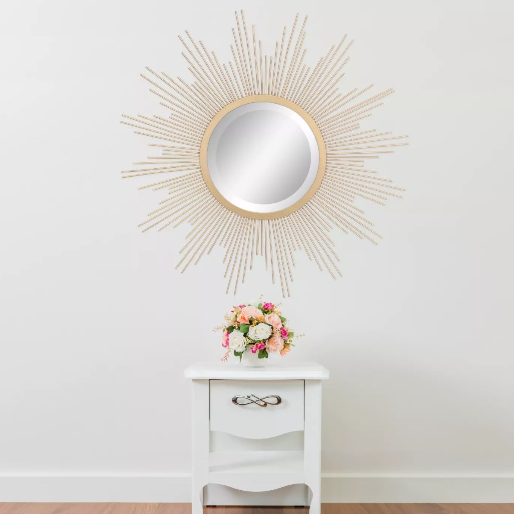 the gold metal mirror on a wall above a small table
