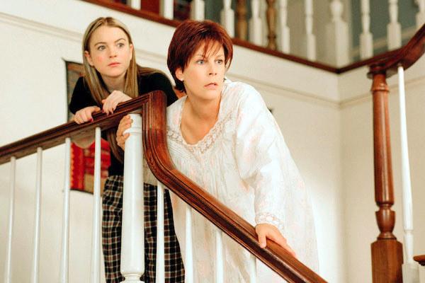 Lindsay Lohan and Jamie Lee Curtis looking shocked on the stairs.