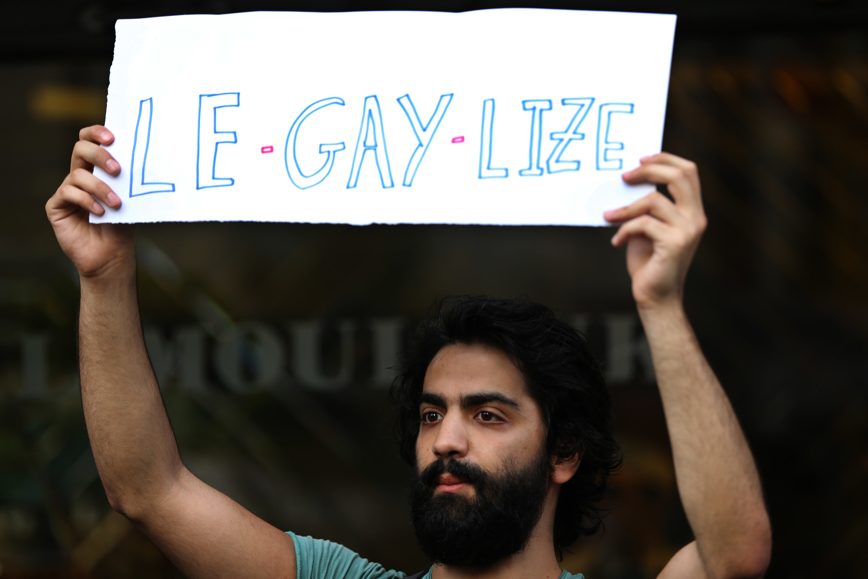 """A protester holds up a sign that says """"Le-gay-lize"""""""