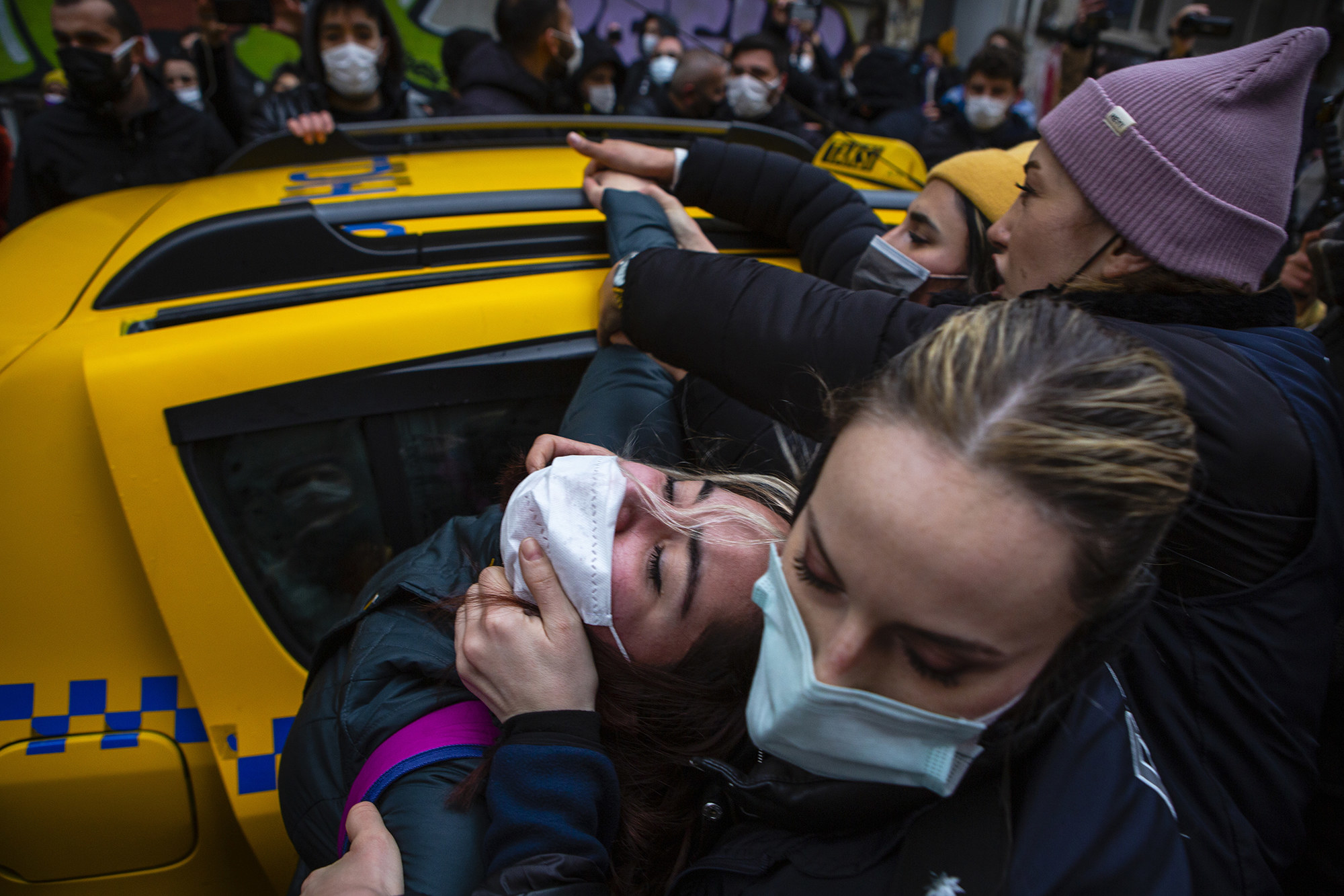 A protester is being pulled from a cab by their face